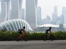 Warga beraktivitas saat kabut asap menyelimuti kota Singapura (15/9/2019). Akibat kabut asap yang terjadi di kota tersebut membuat Grand Prix Formula 1 di Singapura pekan depan, 20-22 September 2019, terancam batal. (AFP Photo/Roslan Rahman)