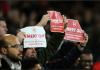 Fans Arsenal mengangkat poster bertuliskan seruan agar Unai Emery segera dipecat. (Sumber: Twitter Arsenal)