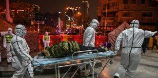 Staf medis berpakaian pelindung membantu menghentikan penyebaran virus mematikan yang dimulai di kota, tiba dengan seorang pasien di Rumah Sakit Palang Merah Wuhan di Wuhan pada 25 Januari 2020.(Foto dari EpochTimes oleh ECTOR RETAMAL / AFP via Getty Images)