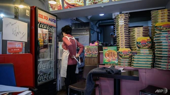 Pemilik restoran pizza Eom Hang-ki (membelakangi lensa).  Dia gembira atas keberhasilan 'Parasite' meraih Oscar yang kemudian berpengaruh terhadap bisnisnya.  (AFP/Ed JONES via CNA)