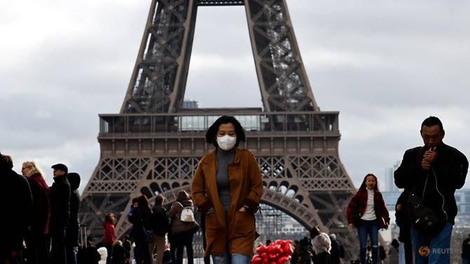 Seorang wanita mengenakan masker pelindung berjalan di Trocadero esplanade di depan Menara Eiffel di Paris, Prancis. (Foto: REUTERS / Gonzalo Fuentes via CNA)