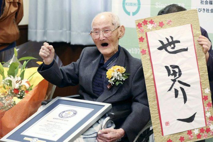 Chitetsu Watanabe (112) berpose di sebelah kaligrafi yang ia tulis setelah dianugerahi sebagai pria tertua di dunia oleh Guinness World Records, di Joetsu, prefektur Niigata, Jepang utara. (Berita Kyodo via AP, File)