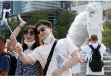 Turis berfoto dengan latar patung Merlion di Singapura. (Foto: China Morning Herald)