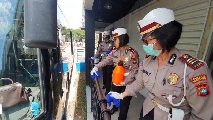 Sat Lantas Polresta Barelang saat Menyemprotkan Cairan Disinfektan ke Bus Trans Batam, Selasa (17/3/2020). (Foto: Suryakepri.com/Romi)