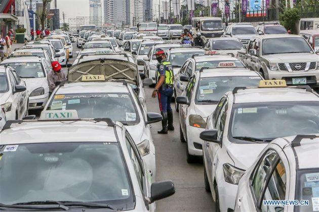 """Seorang polisi berjalan di antasa barisan taksi yang diparkir di sisi jalan setelah pemerintah memerintahkan penangguhan fasilitas angkutan umum massal dengan memperhatikan """"peningkatan karantina masyarakat"""" di Kota Quezon, Filipina pada 17 Maret 2020. Presiden Filipina Rodrigo Duterte pada hari Senin menempatkan seluruh pulau Luzon di Filipina di bawah """"karantina"""" untuk mengekang penyebaran COVID-19. (Xinhua / Rouelle Umali)"""