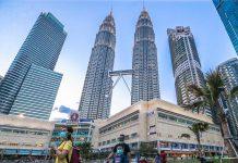 Orang-orang mengenakan masker dengan latarbelakang menara kembar Petronas. di Malaysia. (Foto: Malaysiamail.com)