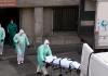 Petugas membawa keluar jenazah dari instalasi pemulasaran jenazah di Madrid, Spanyol. Spanyol adalah negara kedua dengan angka kematian tertinggi setelah Italia akibat wabah Covid-19. (Foto: AFP via SCMP)