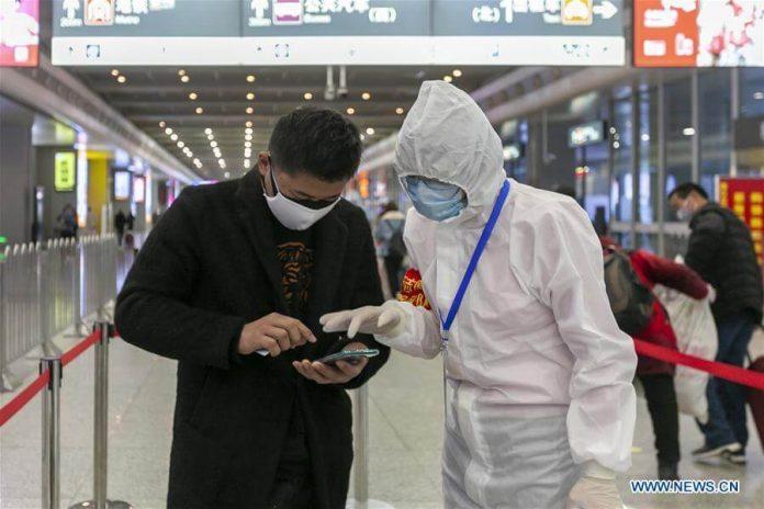 Seorang relawan (kanan) membantu penumpang untuk mendapatkan informasi kesehatannya di Stasiun Kereta Api Shanghai Hongqiao di Shanghai, Cina timur, 5 Maret 2020. Lebih dari 206.900 sukarelawan di Shanghai telah bergabung dalam pertempuran melawan wabah virus corona . (Foto: Wang Xiang / Xinhua)