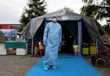 Seorang petugas kesehatan berdiri di depan tenda darurat yang didirikan di luar rumah sakit di kota Brescia, kawasan Lombardy. (Foto: Miguel Medina / AFP via thelocal.it)