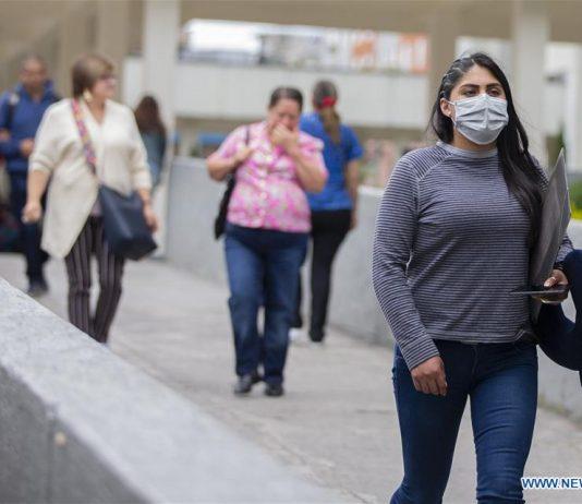 Seorang perempuan di Ecuador mengenakan masker saat berjalan di tengah kota. Sudah 17 kasus infeksi corona di negara Amerika Selatan ini, dengan satu orang dinyatakan meninggal dunia. (Sumber Foto: Standard)