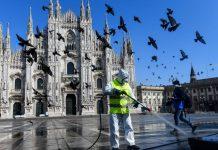 Seorang pekerja menyemprotkan desinfektan di Piazza Duomo di Milan, pada tanggal 31 Maret 2020. FOTO: AFP via strits times.
