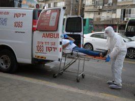 Paramedis Magen David Adom dalam alat pelindung menempatkan seorang pria yang dicurigai memiliki coronavirus ke dalam ambulan di pinggiran Tel Aviv Bnei Brak, 31 Maret 2020. (Gili Yaari / Flash90 via Times of Israel)