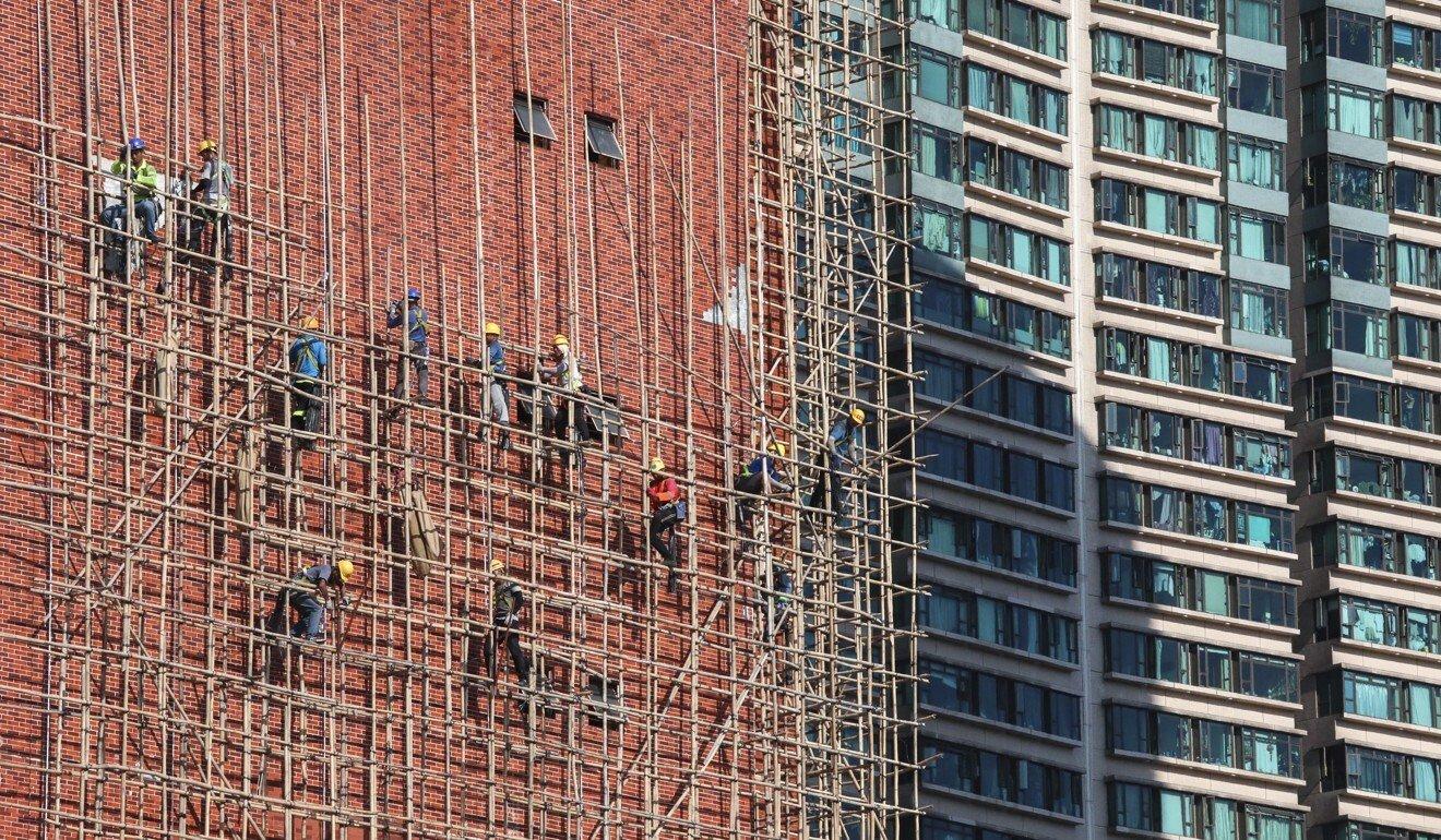 Para pekerja memasang scafolding bambu dalam pembangunan dung pecgedi Hong akar langit di Kong. Foto: Foto: Goldthread via SCMP