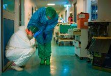 Seorang perawat yang mengenakan masker dan peralatan pelindung menghibur perawat lainnya saat mereka berganti shift pada 13 Maret 2020 di rumah sakit Cremona, tenggara Milan. FOTO: AFP via Straits Times