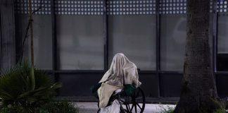 Seorang tunawisma duduk di kursi roda saat cuaca hujan di Sunset Boulevard, Los Angeles, California, pada 6 April 2020. (Foto AP/Damian Dovarganes via FoxNews)