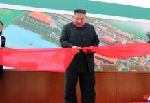 Kim Jong Un menggunting pita saat meresmikan pabrik pupuk di wilayah Suncheon, sekitar 50 kilometer dari ibukota negara, Pyongyang, Jumat (1/5/2020).Fasilitas ini diduga juga melakukan pengayaan uranium untuk senjata nuklir Korut. (Foto: Foto: KCNA / KNS melalui AFP)