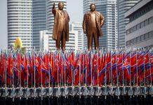 Parade sambil membawa bendera melintasi patung pendiri negara Kim Il Sung (kiri) dan penerus sekaligus anaknya, Kim Jong Il, saat perayaan 105 tahun kelahiran Kim Il Sung di Pyongyang, 15 April 2017. (Foto: REUTERS/Damir Sagolj via ibtimes.sg)