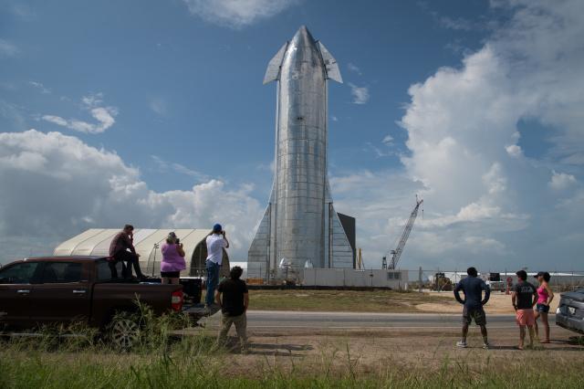 Para pecinta ruang angkasa menyaksikan prototipe pesawat ruang angkasa StarsX di fasilitas peluncuran milik SpaceX pada 28 September 2019 di Boca Chica dekat Brownsville, Texas. Pesawat luar angkasa Starship adalah kendaraan besar yang dimaksudkan untuk membawa orang ke Bulan, Mars, dan sebagainya. (Foto Loren Elliott/Getty Images via engaeget.com)