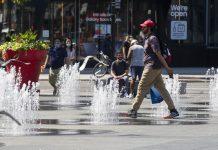 Seorang pria berjalan melalui air mancur di Yonge-Dundas Square di Toronto, Kanada, pada 23 Agustus 2020. (Foto: Zou Zheng / Xinhua)