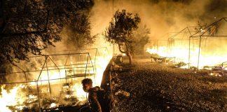 Seorang pencari suaka memandangi kobaran api yng melahap kamp migran Moria pada 9 September 2020 di Lesbos, Yunani. (Foto: Byron Smith/Getty Images via insider)