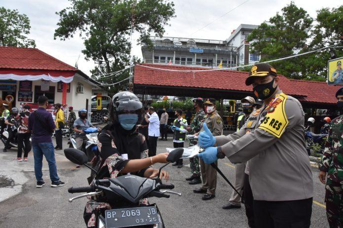 Kapolres Tanjungpinang AKBP Muhammad Iqbal saat membagikan masker gratis kepada pengunjung Polres Tanjungpinang (Suryakepri.com)