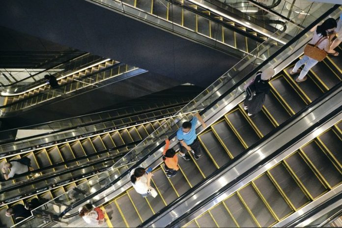 Sejumlah orang naik lift di gedung perbelanjaan di Tokyo pada 24 Agustus 2020. Perekonomian Jepang mencatat rekor penyusutan pada Q2/2020 lebih buruk dari angka 27,8% yang diperkirakan pada bulan lalu. (Foto AP / Eugene Hoshiko)