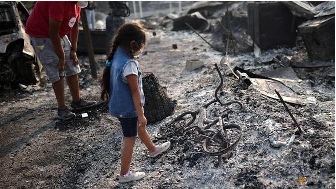 Ashley yang berusia tiga tahun memandangi sepedanya yang terbakar setelah kebakaran hutan menghancurkan lingkungan di Bear Creek, Phoenix, Oregon, pada 10 Sep 2020. (Foto: REUTERS / Carlos Barria via CNA)
