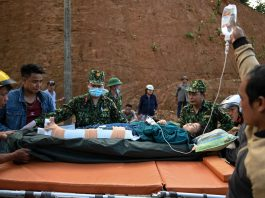 Personil militer pada hari Kamis memindahkan seorang wanita yang telah diselamatkan dari tanah longsor yang dipicu oleh Topan Molave di Provinsi Quang Nam di Vietnam tengah. (Manan Vatsyayana / AFP-Getty Images)