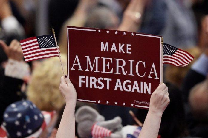 Pendukung Donald Trump mengangkat poster bertuliskan