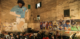 Rabu (25/11/2020) malam, saat kabar kematian Maradona tersebar, orang-orang berkumpul di puncak Quartieri Spagnoli di Napoli, di samping mural bergambar Diego Maradona yang dibuat sejak tahun 1990. (Foto: AFP)