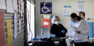 Seorang petugas pemungutan suara menyaksikan seorang pemilih memberikan suaranya pada Hari Pemilihan di balai kota Taylorsville, Georgia. (Foto: Branden Camp/AP via politico.com)