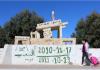 """Seorang gadis berjalan di depan tugu peringatan Mohamed Bouazizi, seorang pedagang kaki lima yang membakar dirinya 10 tahun lalu pada 17 Desember 2010, di Sidi Bouzid, Tunisia. Graffiti berbunyi: """"Yang Diinginkan Rakyat..."""". Foto diambil pada 8 Desember 2020. (REUTERS / Angus McDowall)"""
