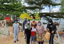 Sofha Marwah Bahtiar berbagi masker di kawasan wisata Kampung Terih, Kelurahan Sambau, Kecamatan Nongsa, Kota Batam.