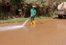 Salah satu petugas pemadam kebakaran yang membersihkan tanah di jalan Punggur