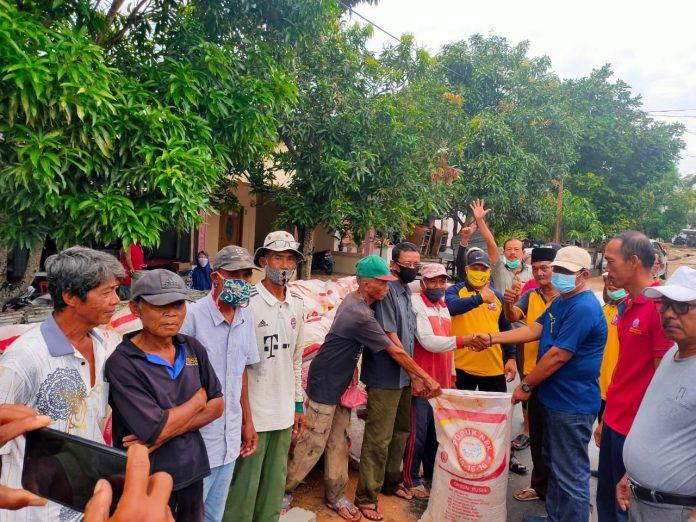 Ketua DPRD Karimun Muhammad Yusuf Sirat (kaos biru) menyerahkan bantuan 252 karung pupuk kepada Kelompok Tani Karya Maju Jaya Desa Pangke, Kamis (24/12/2020). Foto Suryakepri.com/IST