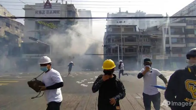Pengunjuk rasa anti-kudeta bereaksi ketika asap dari gas air mata naik di Yangon, Myanmar Minggu, 28 Februari 2021. (AP Phoro via CNA)