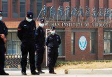 Staf keamanan berjaga di luar Laboratorium Institut Virologi Wuhan selama kunjungan tim WHO. (Foto dari Sky News)