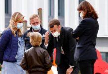 Presiden Prancis Emmanuel Macron berbicara dengan seorang anak saat dia mengunjungi departemen psikiatri anak di rumah sakit Reims, Prancis timur, pada 14 April 2021. (Foto: Christian Hartmann / Pool via AP)