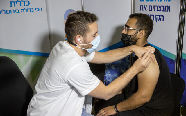 Seorang pria Israel menerima suntikan COVID-19 di pusat vaksinasi di Yerusalem, pada 11 Maret 2021. (Yonatan Sindel / Flash90)