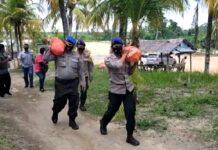 Sejumlah anggota Satpolairud Polres Karimun membagikan paket sembako gratis kepada masyarakat di Kecamatan Meral. Foto Suryakepri.com/IST