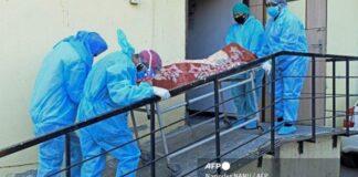 Anggota staf medis yang mengenakan APD membawa jenazah pasien Covid-19 di sebuah rumah sakit di Amritsar, India pada 24 April 2021.