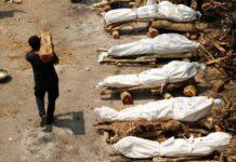 Seorang pria membawa kayu berjalan melewati tumpukan kayu pemakaman orang-orang yang meninggal karena Covid-19 saat kremasi massal, di sebuah krematorium di New Delhi, India, 26 April 2021. /Reuters/Adnan Abidi