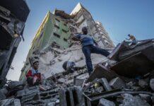 Warga Palestina di antara reruntuhan bangunan di Kota Gaza pada Rabu (19/5/2021) sore. (Foto: Mohammed Sabre / EPA via Guardian)