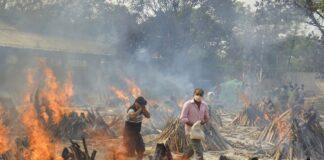 Kerabat korban meninggal menghindari sengatan panas dari beberapa tumpukan kayu pemakaman korban Covid-19 di sebuah krematorium di pinggiran New Delhi, India. (KC/AP)