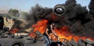 Seorang demonstran Palestina melempar ban yang terbakar ke tumpukan selama bentrokan dengan pasukan Israel di dekat pemukiman Yahudi Beit El dekat Ramallah di Tepi Barat pada 14 Mei 2021. (ABBAS MOMANI / AFP)