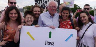 """Ilustrasi: Senator Vermont Bernie Sanders berfoto dengan aktivis IfNotNow di New Hampshire, termasuk mahasiswa Universitas Michigan Becca Lubow di paling kiri, dan memegang tanda bertuliskan """"Orang Yahudi Menentang Okupasi"""" (Istimewa / IfNotNow)"""