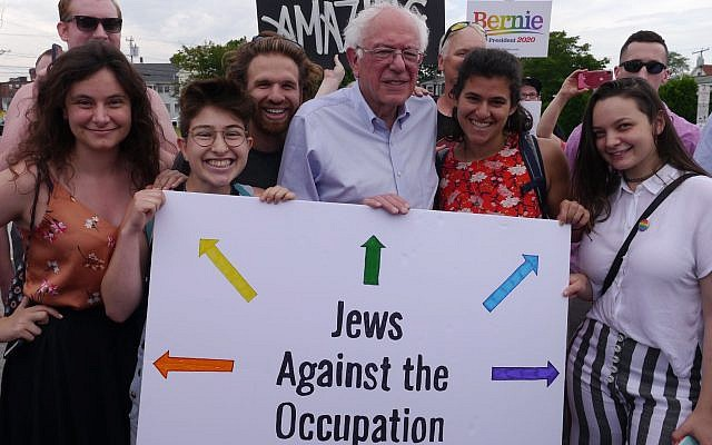 Ilustrasi: Senator Vermont Bernie Sanders berfoto dengan aktivis IfNotNow di New Hampshire, termasuk mahasiswa Universitas Michigan Becca Lubow di paling kiri, dan memegang tanda bertuliskan