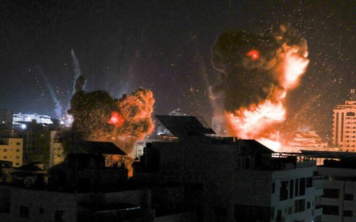 Ledakan menerangi langit malam di atas gedung-gedung di Kota Gaza saat pasukan Israel melakukan serangan di daerah kantong Palestina, pada awal 18 Mei 2021. (MAHMUD HAMS / AFP via Times of Israel)