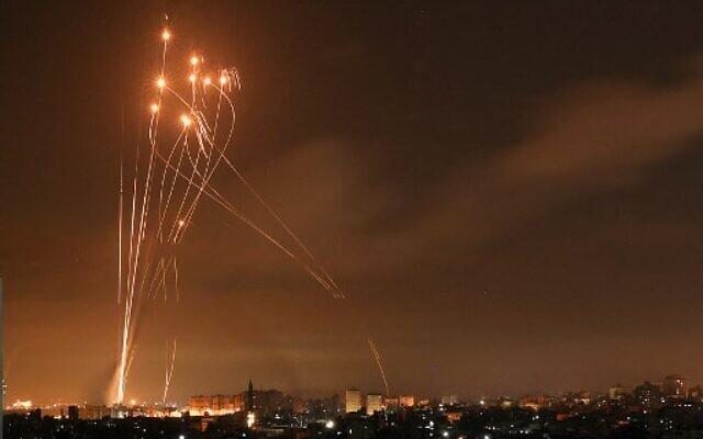 Roket Hamas dan pencegat Iron Dome menerangi langit malam di atas Jalur Gaza utara pada 14 Mei 2021. (Foto oleh MOHAMMED ABED / AFP)