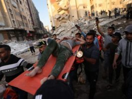 Warga Palestina membawa salah satu korban selamat dari bawah reruntuhan sebuah bangunan, setelah dihantam oleh serangan Israel, di Kota Gaza, 16 Mei 2021 (Foto oleh MOHAMMED ABED / AFP)